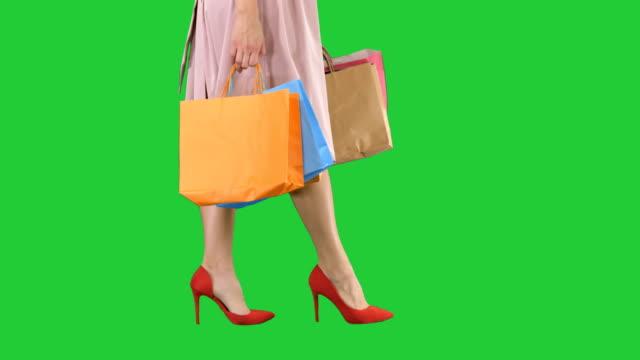 en del kropp, vackra kvinnliga slanka ben sexig tjej håller ett papper shoppingkassar på en grön skärm, chroma key - köpnarkoman bildbanksvideor och videomaterial från bakom kulisserna