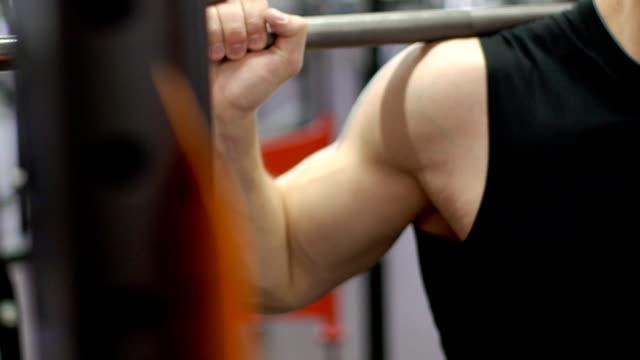 teil des männlichen stamm, die duckt sich mit langhantel auf schultern in turnhalle - fitnessausrüstung stock-videos und b-roll-filmmaterial