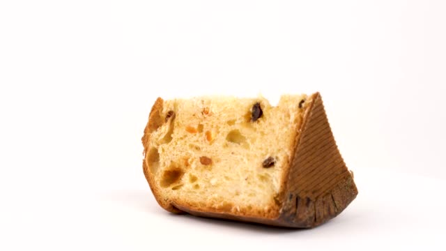 part of panettone with raisins and dried apricots rotating in turn table isolated on white background. - panettone video stock e b–roll