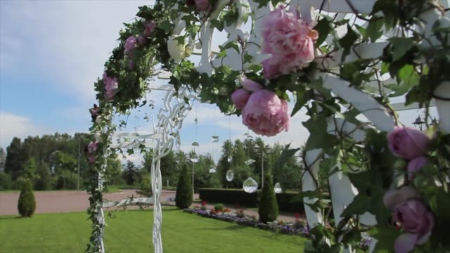 part of the festive decor, floral arrangement. detail of a wedding arch. wedding decoration ceremony chandelier in the arch of flowers . wedding decoration. arch. cage. wedding setup on the beach. wedding arch decorated with flowers. diamonds - дворец спорта стоковые видео и кадры b-roll