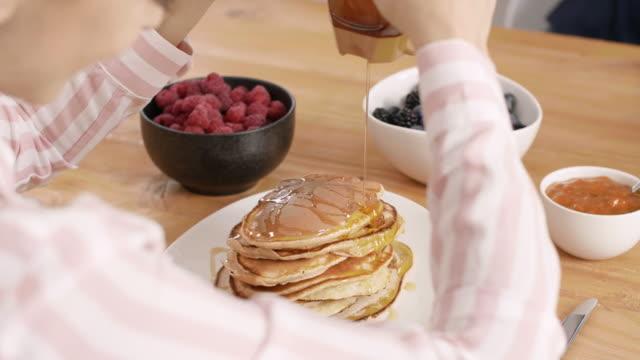 part of woman eating pancake at kitchen - pancake video stock e b–roll