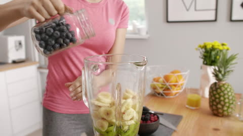 parte della donna che prepara frullato di frutta in cucina - alimentazione sana video stock e b–roll
