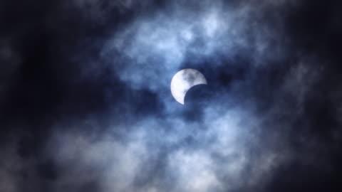 vidéos et rushes de éclipse solaire partielle en couleur foncée bleue avec le nuage mobile - vue partielle