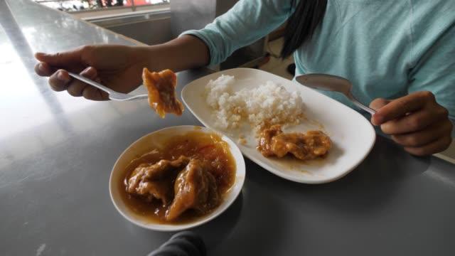 vidéos et rushes de vue partielle d'une jeune femme mangeant le bifteck de porc et le riz sur la table. - fourchette