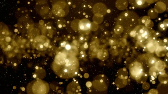 partikel gold-glitzer bokeh vergeben staub abstrakten hintergrund schleife - fülle stock-videos und b-roll-filmmaterial
