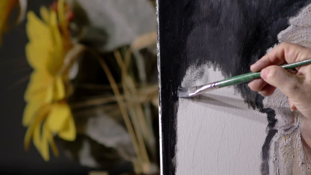 particular on hand of woman using brush on canvas video