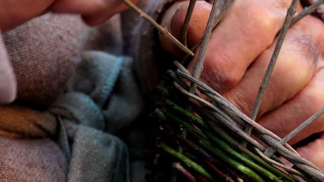 particular on hands of a elderly man weaving a basket with gorse - halmslöjd bildbanksvideor och videomaterial från bakom kulisserna