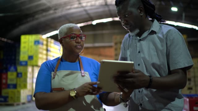 partners / coworkers walking and using digital tablet at warehouse - prodotti supermercato video stock e b–roll