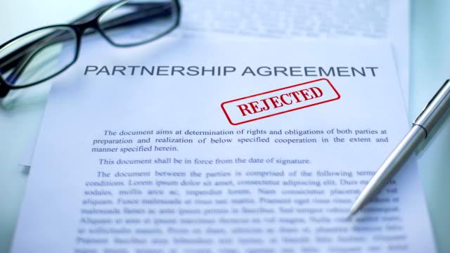 vidéos et rushes de accord de partenariat a rejeté, main piétinement sceau sur le document d'entreprise, closeup - notaire