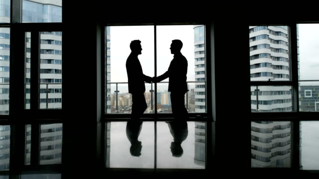 partnership concept: two man silhouette handshake - team video stock e b–roll