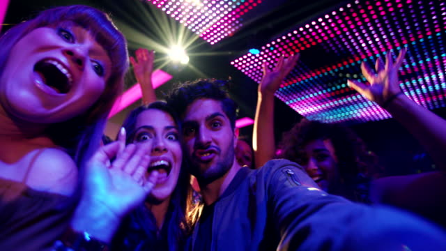 Party Couple making silly faces for selfie in night club Fashionable friends at nightclub taking selfies and pulling faces for the photo with people, music and disco lights in the background of the party in the night club party stock videos & royalty-free footage