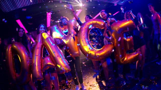 Fiesta en Club nocturno de danza de globos con amigos sosteniendo - vídeo