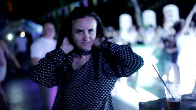 stockvideo's en b-roll-footage met partij op straat. meisje dansen in de menigte op een openlucht disco. de dansende meisjes in een disco. - martini