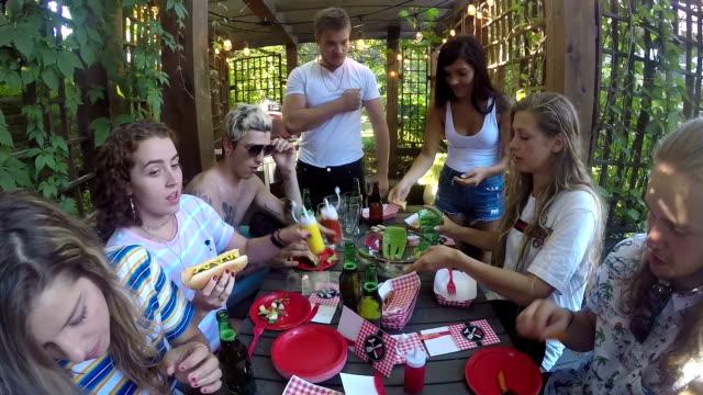 vídeos de stock, filmes e b-roll de festa de cachorro-quente adultos jovens de verão ao ar livre para churrasco - cachorro quente