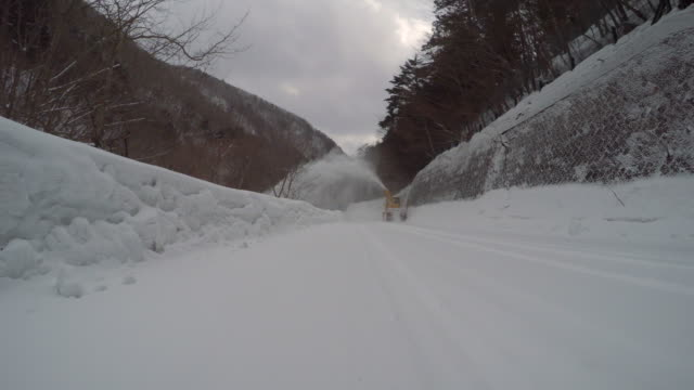 pass a snowplow at snow mountain road -4K- video