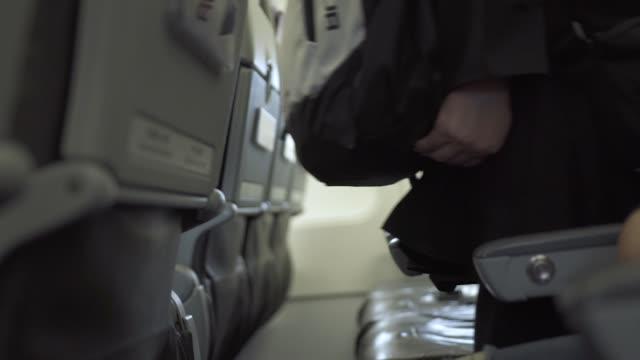 passangers boarding in airplane in airport. passangers walking to seats inside aircraft cabin in airport - wchodzić na pokład filmów i materiałów b-roll