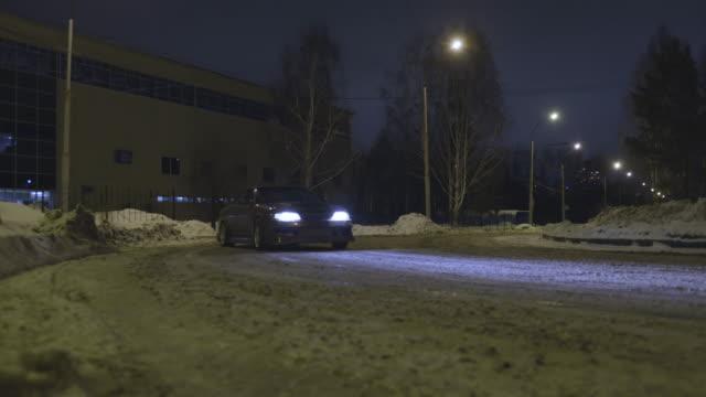vídeos y material grabado en eventos de stock de coche de pasajeros a la deriva en una carretera nevada en la calle de la ciudad por la noche, carrera peligrosa. acción. un coche entrando en un patín mientras se gira en la oscuridad - nieve amontonada