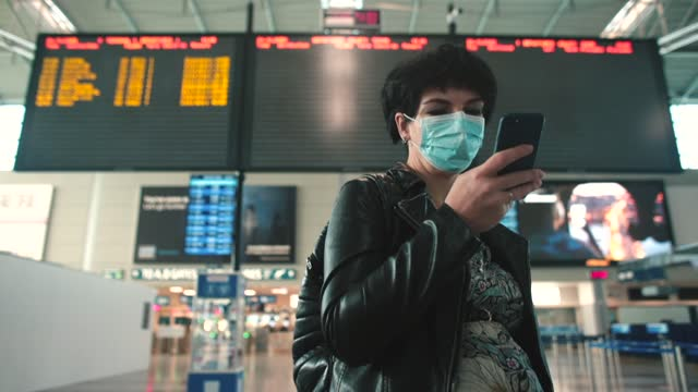Passenger in mask uses app on phone to search tickets sales. Flights canceled.