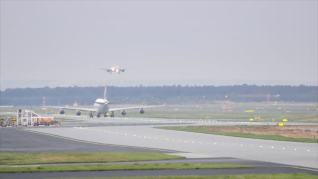 Passenger plane landing, busy tarmac, airport lights at early morning video