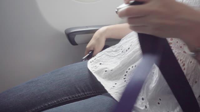비행기 안전 벨트 자물쇠를 준비 하는 승객 - airplane seat 스톡 비디오 및 b-롤 화면