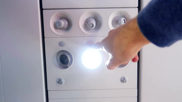 passenger switches off reading lamp in airplane overhead panel - stock video - sedili aereo video stock e b–roll