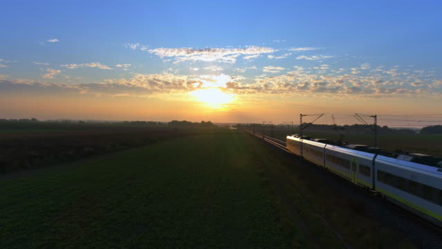 passenger train passing through countryside at sunset - поезд стоковые видео и кадры b-roll
