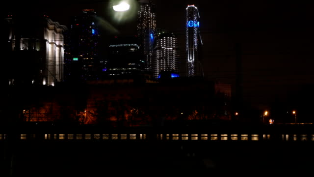 Passenger train passing through the city at night Passenger train passing slowly through the city at night. Modern illuminated skyscrapers in background intercity stock videos & royalty-free footage