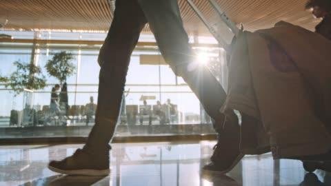 vídeos y material grabado en eventos de stock de slo mo ds pasajeros caminando por el aeropuerto con una bolsa de viaje con ruedas y el sol brillando detrás de él - viajes