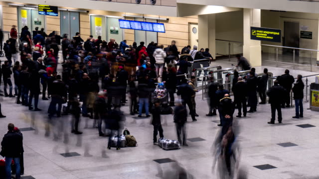 Passengers and greeters in the arrivals area of the airport, time lapse