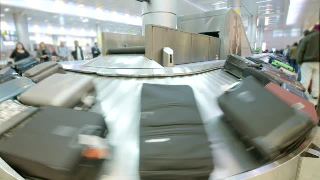 passengers collecting luggage from a conveyor belt at the airport - табло вылетов и прилётов стоковые видео и кадры b-roll
