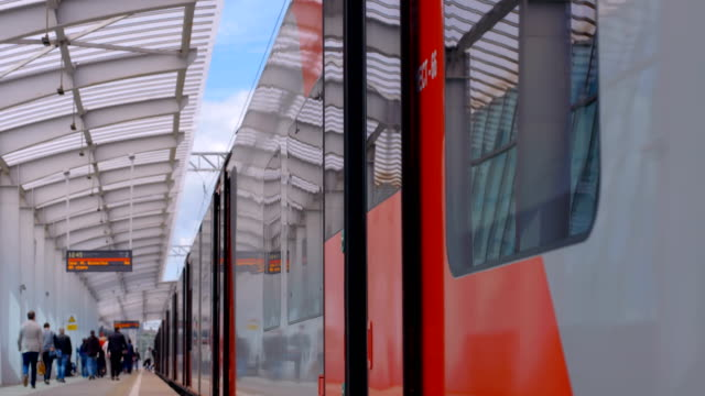 Passengers got out the train and walk along the platform of the metro station Passengers got out the train and walk along the platform of the ground metro station, train doors are closing subway platform stock videos & royalty-free footage