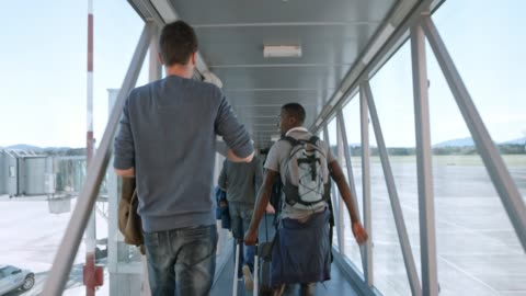 passeggeri slo mo che si affrettano a attraversare il ponte del jet per salire a bordo dell'aereo - aeroporto video stock e b–roll