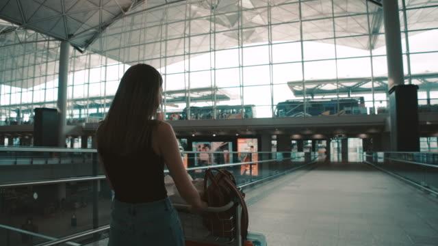 passagiere der fluggesellschaft gingen, um das gepäck zum gate zu schleppen. in der passagierhalle - wohngebäude innenansicht stock-videos und b-roll-filmmaterial