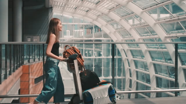 Passengers in the airline walked to drag the luggage to the gate. In the passenger hall Woman walked to drag the luggage to the Check-in gate. woman pushing cart stock videos & royalty-free footage