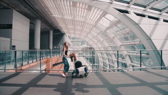 stockvideo's en b-roll-footage met passagiers in de luchtvaartmaatschappij liepen om de bagage te slepen naar de poort. in de passagiers zaal - vliegveld vertrekhal