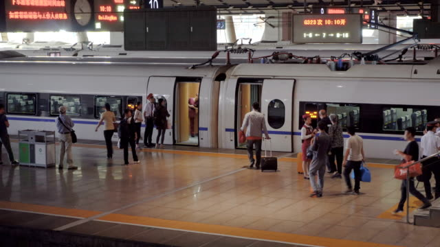Passengers on platform boarding China high speed rail. Chinese people get on Gaotie train in Beijing, walking along platform, checking tickets and entering the train. railroad station platform stock videos & royalty-free footage