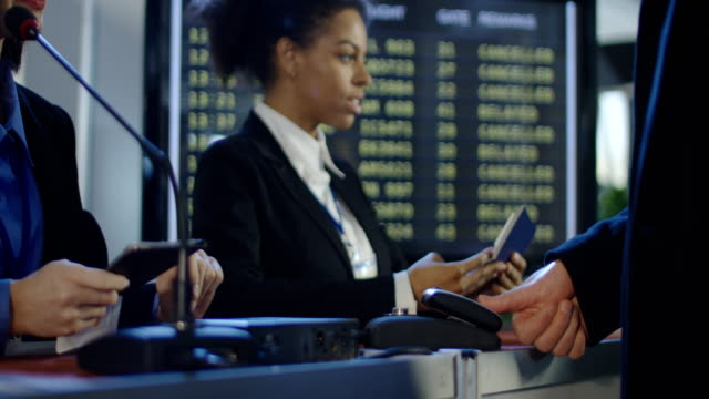 Passengers passing biometric control in airport Crop view of people passing through registration counter with multiracial receptionists in airport having biometric control. 4K shot on Red cinema camera. passport stock videos & royalty-free footage