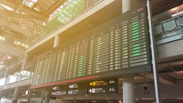Passenger's pov at Suvarnabhumi Airport arrival board, flight information updating real time. Destinations, flight status, boarding gates info change on screen.