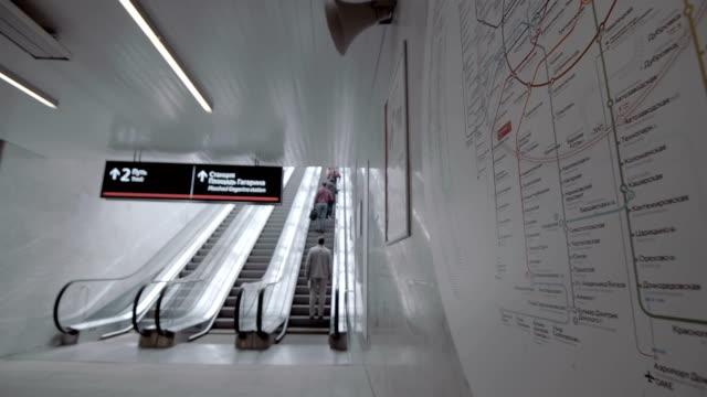 passagerare rida på rulltrappan upp till stationen av marken metro - billboard train station bildbanksvideor och videomaterial från bakom kulisserna