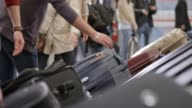 istock Passengers taking their luggage off the baggage carousel at the airport 933320678