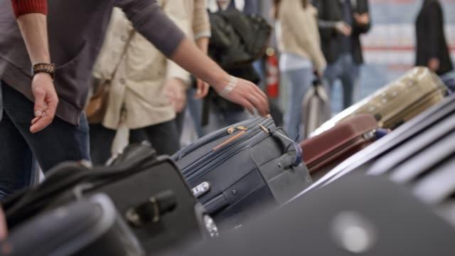 공항에서 수하물 컨베이어에서 수하물을 복용 하는 승객 - 공항 스톡 비디오 및 b-롤 화면