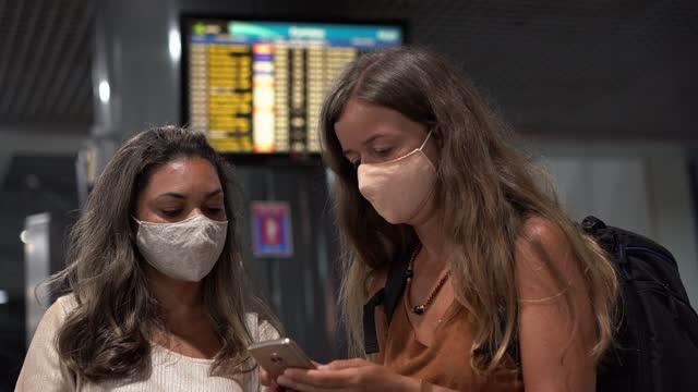 Passengers waiting near the flight information panel