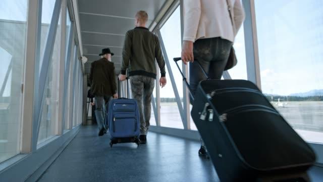 havaalanında bir cam jet köprü yürüyüş yolcu - turistik yer stok videoları ve detay görüntü çekimi