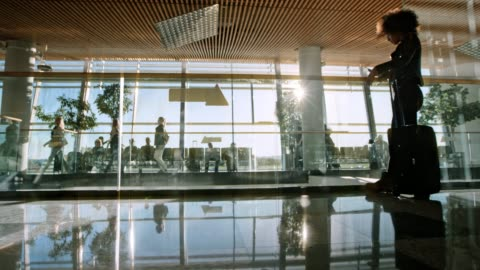 ds passeggeri che camminano nel terminal dell'aeroporto con il sole che splende attraverso grandi finestre di vetro - aeroporto video stock e b–roll
