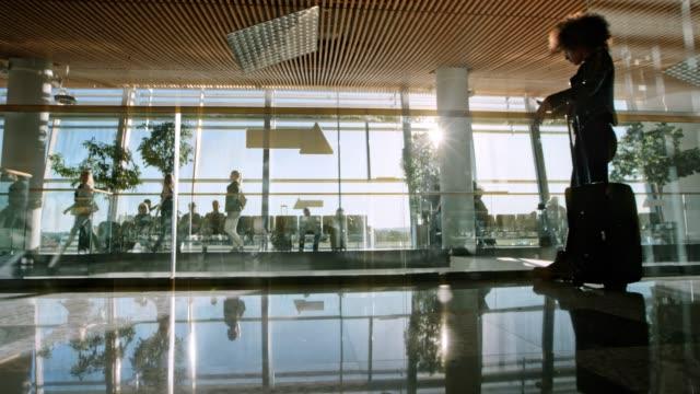 stockvideo's en b-roll-footage met ds passagiers lopen in de luchthaventerminal met zon schijnt door de grote glazen ramen - vliegveld vertrekhal