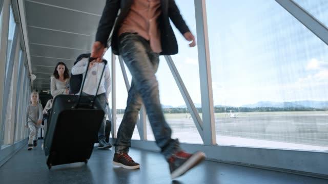 Passengers walking in the glass boarding bridge