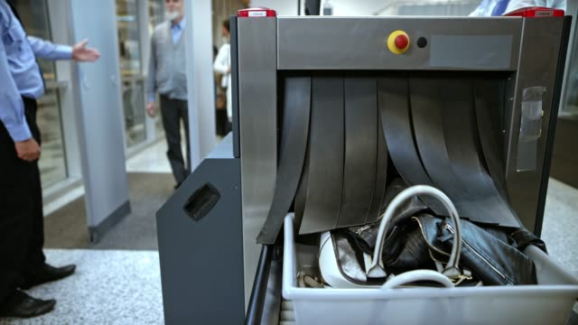 TIME-LAPSE Passengers walking through metal detector at the airport security and luggage is being scanned
