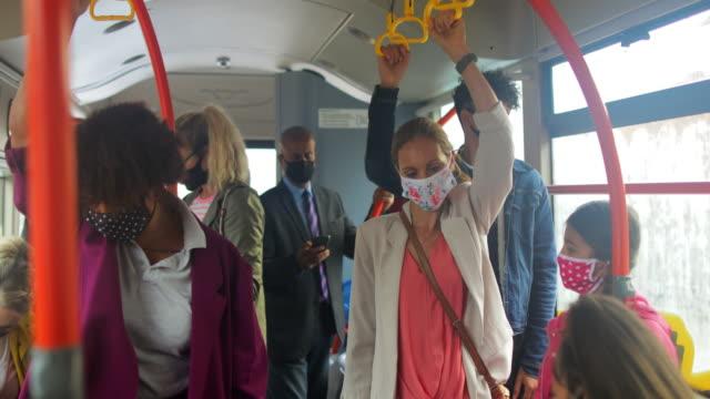 passeggeri che indossano maschere durante l'ora di punta - autobus video stock e b–roll