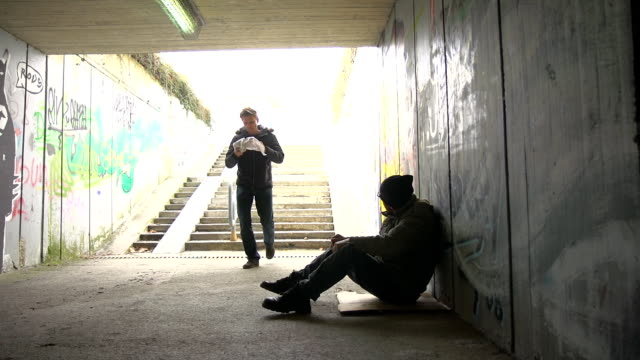 HD: Passer-By Giving Food To A Homeless Person HD1080p: Passer-by giving his food to a homeless person begging in the underpass. giving stock videos & royalty-free footage