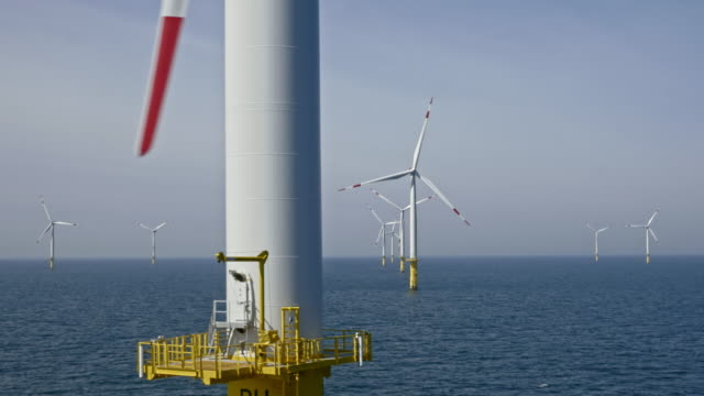 AERIAL Passing a wind turbine tower at sea